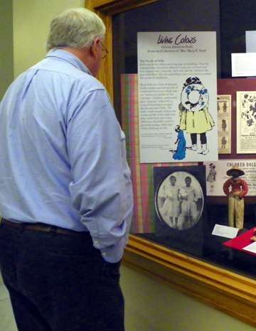 Kim Combs, Publisher of Help YourSelf, views one of the 4 showcased exhibits of Black Dolls on display at the Arkansas State Capitol thrugh February 2015.